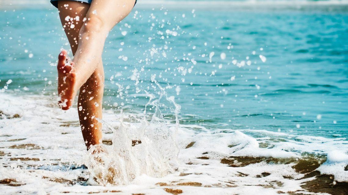 ragazza-che-calcia-acqua-mare-jeans-corti-gambe-nude